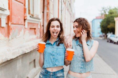 Photo pour Belles filles, copines Brunettes, boire du café dans la rue dans les verres et sourire - image libre de droit