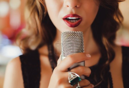 beautiful girl singing into  microphone