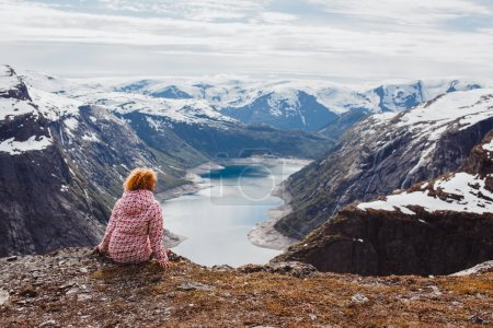 Photo pour Young red girl   on a rock and watching the sunset and the mountains, overnight in tent a trip to the mountains, the language of the Troll, Norway fjords, cold weather - image libre de droit