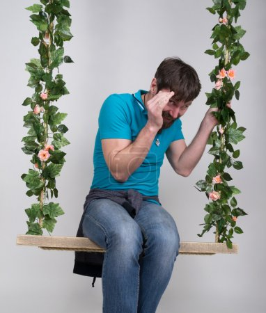 bearded man in jeans, swinging on swings and hamming to the camera. wooden swing suspended from a rope hemp, rope wrapped vine and ivy. different emotions