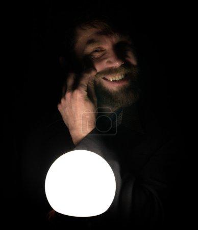 Photo pour L'homme barbu dans l'obscurité, tenant devant une lampe, exprime différentes émotions. virevoltant sa moustache avec vos doigts - image libre de droit