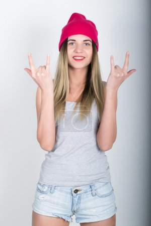 teenager girl in denim shorts and a gray T-shirt and a pink knit hat, tied at the hips plaid shirt. showing sign heavy metal
