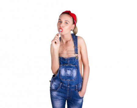 Photo for Beautiful young leggy blondy girl in a red bandana, denim overalls over his naked body, licking candy. isolated on white background. - Royalty Free Image
