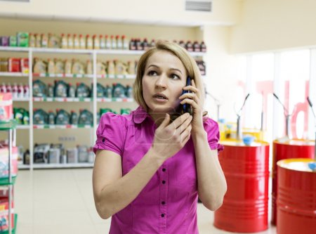blonde girl chooses motor oil in auto parts store, consults by phone
