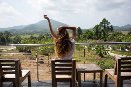 The long-haired girl in cafe overlooking mountains, the happy girl, in white poppy, the pensive woman. Swinging hands.