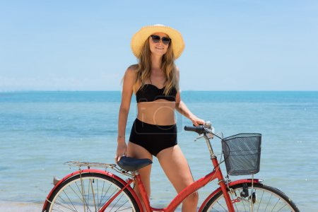 The beauty riding a bicycle on the beach at sunset,the stylish girl by her bicycle, the beach cruiser bicycle, a road bicycle look of style,the kind stylish woman in a hat sports,Thailand,island Samui