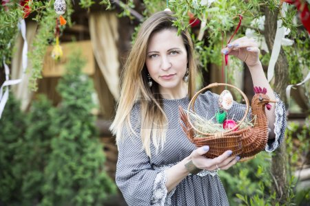 Young beautiful girl with a basket with Easter eggs on background Easter tree