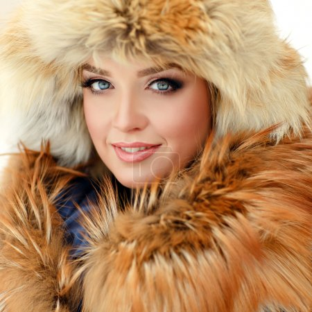 Portrait of a beautiful glamorous girl in a fur hat and a red co