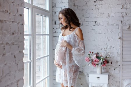 Beautiful soft and sensual pregnant girl in white transparent dr