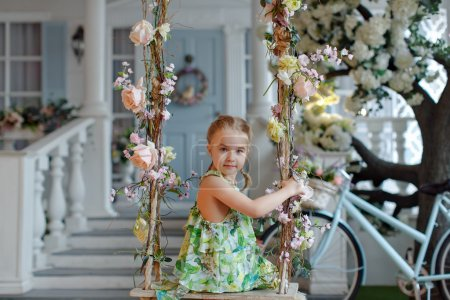 Cute little girl in a green dress sitting on swings decorated wi