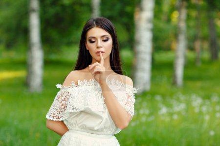 Portrait of beautiful sensual brunette girl in white dress, put