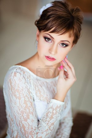 Portrait of beautiful young brown-haired woman in white dress