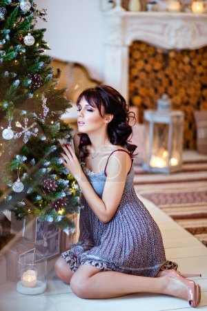 Beautiful brunette girl in a grey dress sitting near the Christmas tree