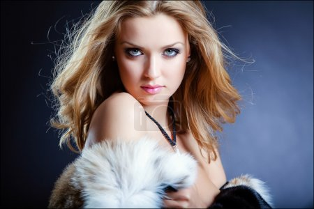 Sensual sexy girl blonde in a fur coat on a blue background, close up