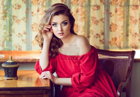 Portrait of a very beautiful sensual girl in a red dress with bare shoulder, sitting on a chair