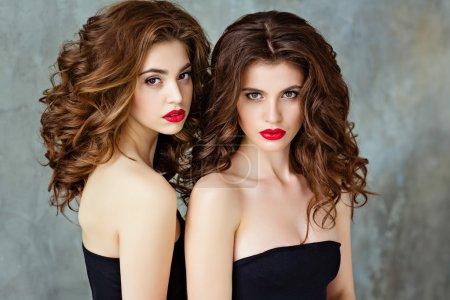 Photo pour Portrait de deux belle brune glamour et sensuelle aux magnifiques cheveux bouclés et au maquillage éclatant au rouge à lèvres, gros plan, en studio sur fond gris, beauté - image libre de droit