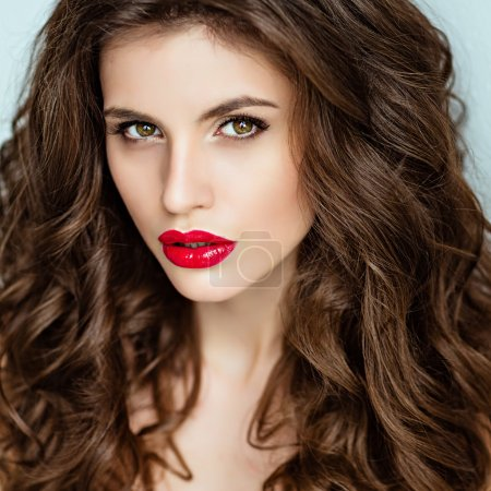 Portrait of a beautiful glamorous brunette with curly hair and b