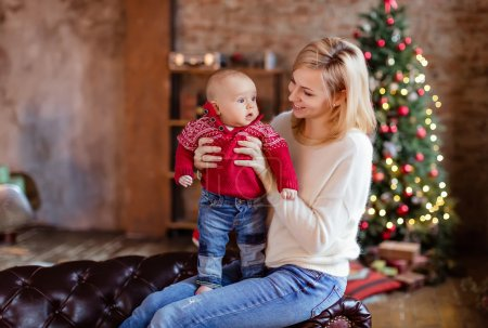 Photo pour Charmante mère blonde dans le pull blanc regarde son petit fils tout-petit dans un pull rouge et souriant sur le fond des arbres de Noël et des guirlandes dans la maison - image libre de droit