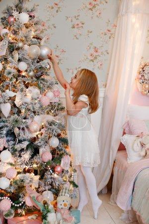 Photo pour Très belle petite fille blonde charmante dans une robe blanche atteignant des jouets et des boules sur le fond des arbres de Noël à l'intérieur de la maison - image libre de droit