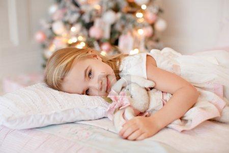 Photo pour Très belle petite fille charmante blonde en robe blanche couchée sur le lit et semble triste sur l'image sur le fond des arbres de Noël à l'intérieur lumineux de la maison - image libre de droit