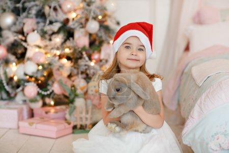 Photo pour Très jolie petite fille blonde en robe blanche et chapeau de Père Noël tient un lapin vivant sur le fond des arbres de Noël à l'intérieur de la maison - image libre de droit