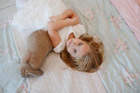Photo pour Très jolie petite fille blonde en robe blanche couchée sur un lit à côté d'un lapin vivant dans un intérieur lumineux de la maison - image libre de droit