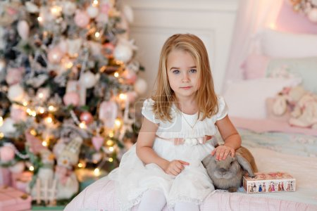 Photo pour Très jolie petite fille blonde en robe blanche rit et tient un lapin sur un fond d'arbres de Noël à l'intérieur de la maison - image libre de droit