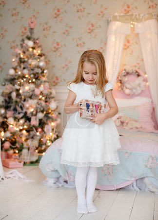 Very cute little girl blonde in a white dress holding a gift boxes on a background of Christmas trees in the interior of the house