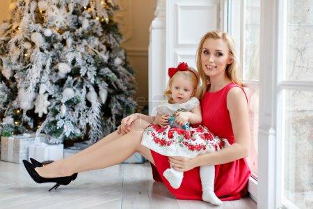 Photo pour Mère en robe rouge sourit et tient une belle petite fille blonde aux yeux bleus, sur un fond d'arbres de Noël à l'intérieur de la maison - image libre de droit