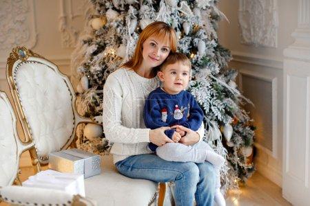 Photo pour Mère dans un pull blanc sourit et tient un charmant bébé garçon en pull bleu sur fond d'arbres de Noël à l'intérieur de la maison - image libre de droit