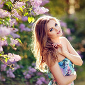 Beautiful glamorous red-haired girl in a bright dress stands near a Bush of lilacs in the summer