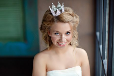 Close-up portrait of a smiling young blonde woman with full lips, wearing a white dress and a crown on his head like a princess