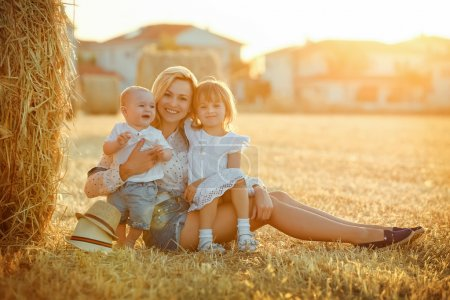 Photo for A young mother with two children - a little baby boy and a girl in a white dress sitting on a background of straw fields at sunset and smile - Royalty Free Image