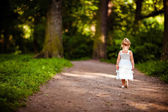 cute little blonde girl in a white dress walking down the path in the forest, the view from the back