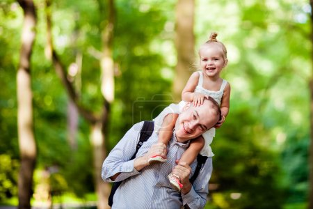 Dad holding his daughter on his shoulders and a happy smile