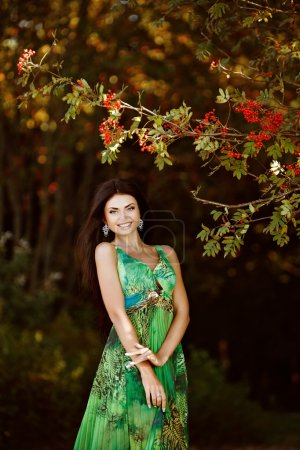 Portrait of a sexy sensual very beautiful smiling brunette girl with long hair in a green dress in nature about Rowan