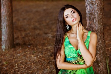 Portrait of a sexy sensual very beautiful brunette girl with long hair in a green dress in nature, close up