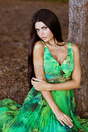 portrait of a sexy sensual very beautiful brunette girl with long hair in a green dress