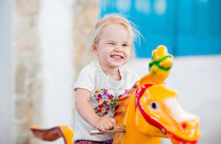 Emotional little girl riding on the carousel