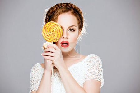 Beautiful red-haired girl holding a Lollipop