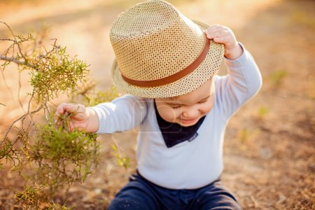 Little adorable baby boy in a straw hat and blue shirt sitting near a tree on the ground at sunset in the summer, and tries to take off his hat
