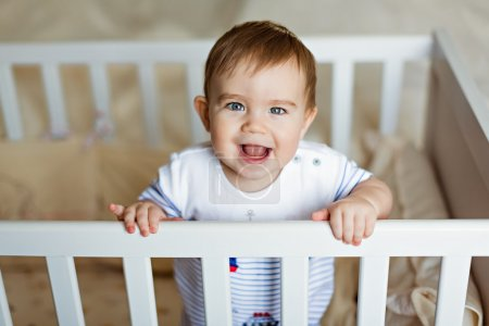 Little cute adorable little blond boy in a striped bodykit is in the nursery with white crib and laughs