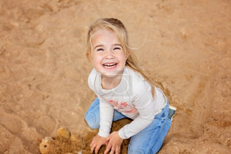 Little girl little girl sitting on the sand on the beach and gris, playing with the sand in the summer