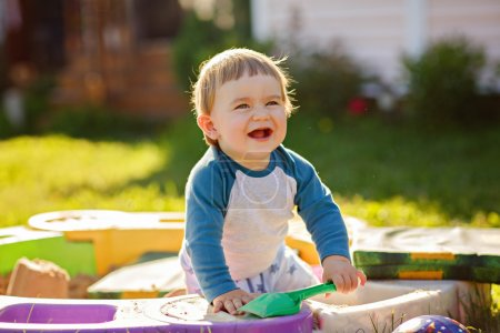 Little chubby baby boy laughs, sitting in the sandbox in the summer in Sunny weather