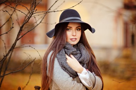 Photo for Portrait of a very beautiful young brunette woman with shiny straight hair in a gray coat and black hat on a background of the autumn landscape in the park - Royalty Free Image