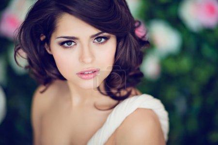 Very beautiful girl brunette in a beige dress looks straight, cl
