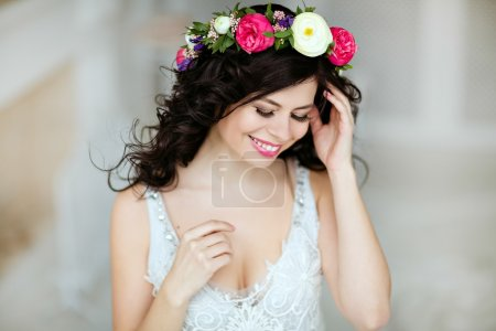 Portrait of a sensual beautiful brunette girl with a wreath of f