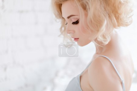 Portrait of a beautiful sensual and sexy blonde girl on white ba