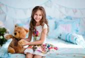 Velmi roztomilé kudrnaté vlasy dívka sedící na posteli s měkkou t