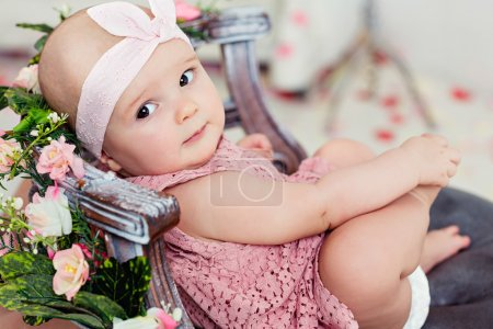 Small very cute wide-eyed smiling baby girl in a pink dress is i